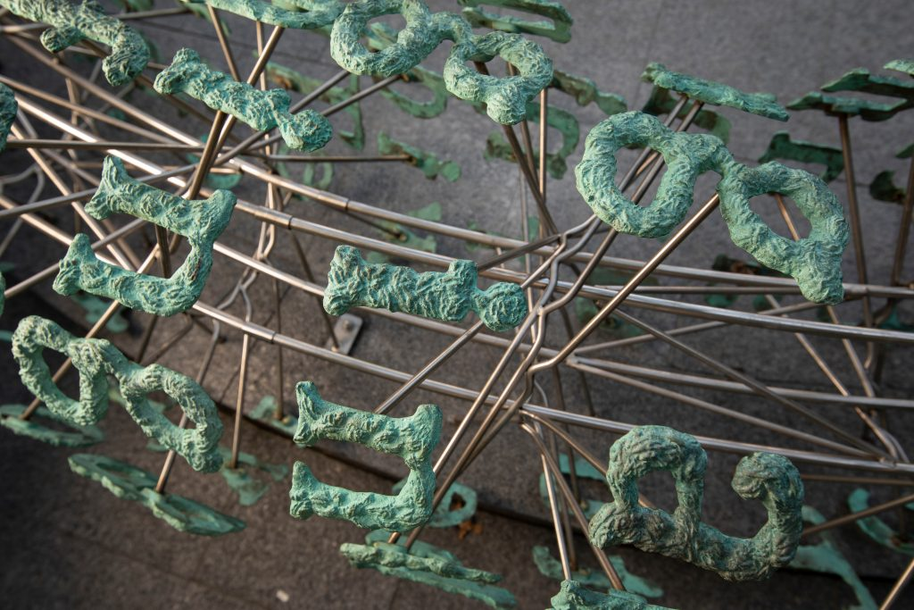 A zoom into the fine details of the patinated finish of the letters that make up Broken English