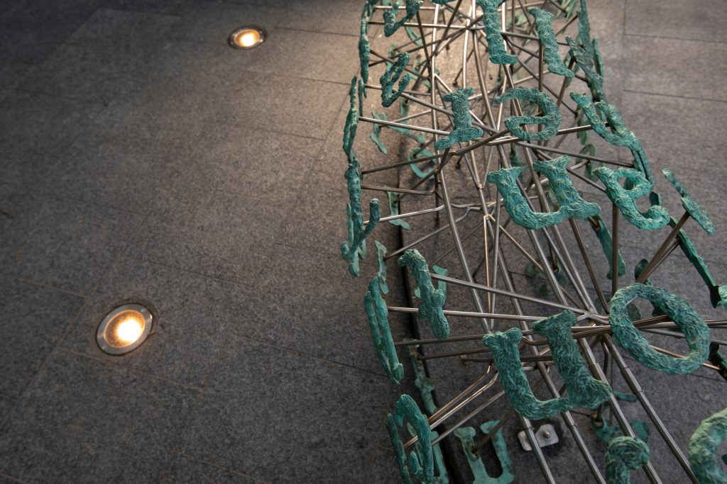 A angle from above showing how the sculpture is displayed surrounded by small lights inserted in the ground